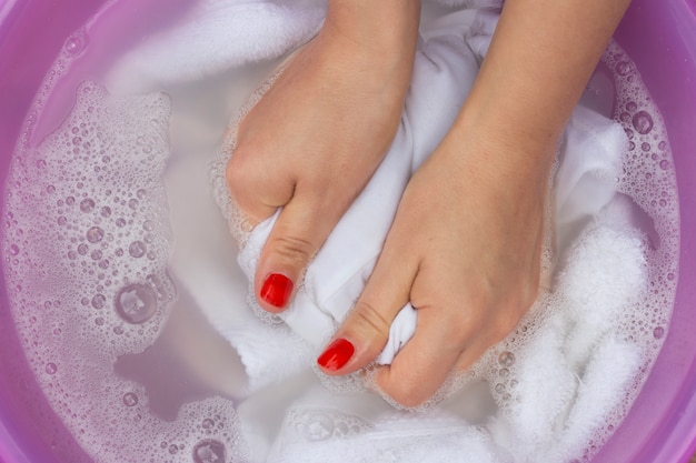Mani femminili che lavano i vestiti bianchi nel bacino