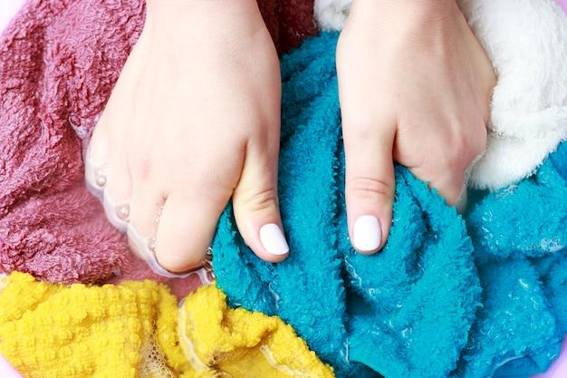 Mani femminili che lavano i vestiti multicolori in bacino