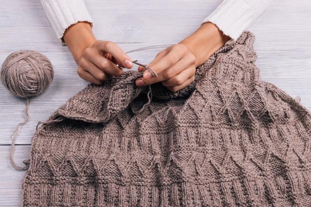 Mani femminili che lavorano a maglia maglione di lana