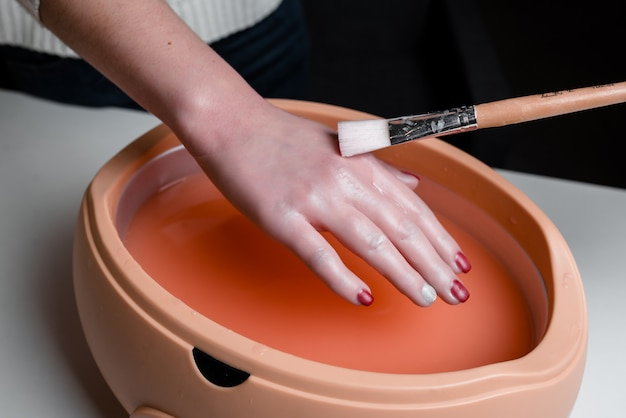 Mani femminili che prendono procedura in una ciotola lilla della cera paraffinica. attrezzature per cosmetica e cura della pelle in un salone di bellezza spa.