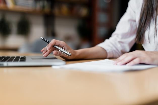 Mani femminili che scorrono sul computer portatile e che prendono le note con la penna
