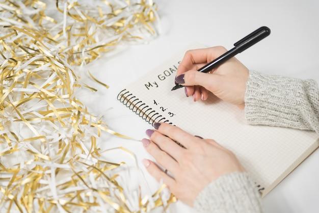 Mani femminili che scrivono i miei obiettivi in un taccuino.