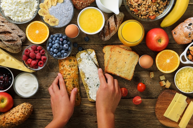 Mani femminili che spandono burro sul pane. muesli, uova, noci, frutta, bacche, latte, yogurt, succo di frutta, formaggio.