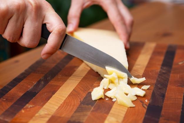 Mani femminili che tagliano parmigiano sul bordo di legno