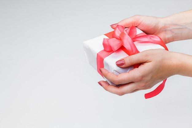 Mani femminili che tengono confezione regalo