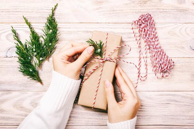 Mani femminili che tengono disposizione piana del regalo di natale o del nuovo anno. vista superiore fatta a mano del contenitore di regalo di celebrazione di festa del modello e dei coni di abete. tonica