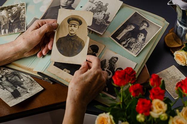Mani femminili che tengono e vecchia foto di suo nonno. album fotografico vintage con foto. concetto di valori familiari e di vita.