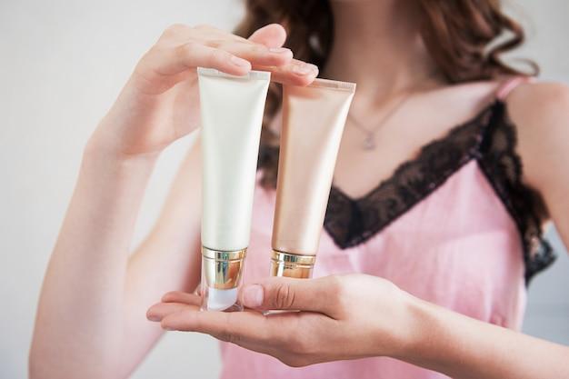 Mani femminili che tengono i tubi crema cosmetici.
