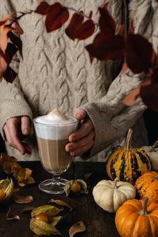 Mani femminili che tengono il cappuccino fumante, caffè con zucche, foglie di autunno del latte sul tavolo di legno