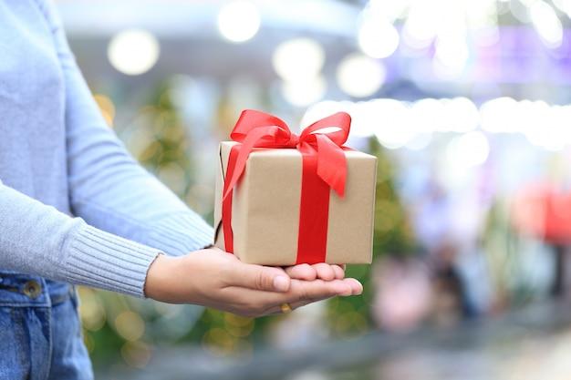 Mani femminili che tengono il contenitore di regalo con il nastro rosso per il natale e capodanno o la stagione di saluto, giorno di biglietti di s. valentino