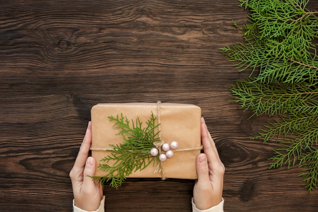 Mani femminili che tengono il contenitore di regalo di natale su legno scuro