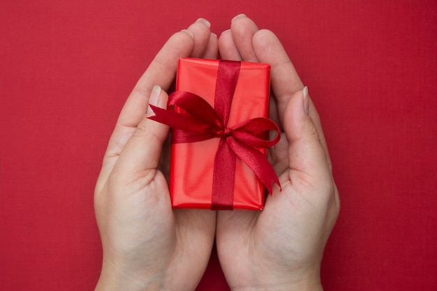Mani femminili che tengono il contenitore di regalo rosso di natale con il nastro e l'arco rossi, sopra priorità bassa rossa.