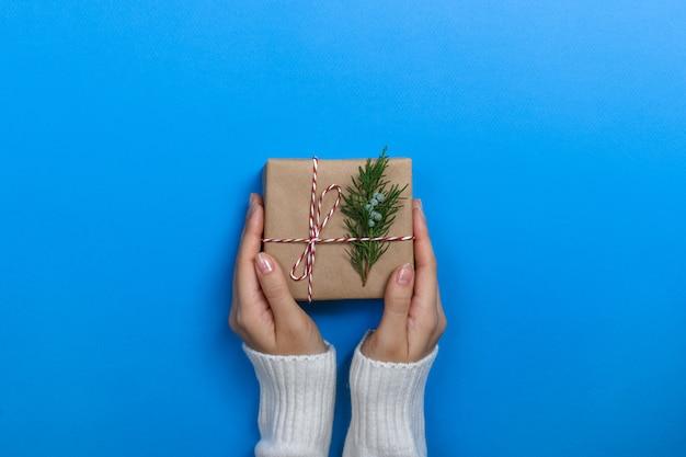 Mani femminili che tengono il contenitore di regalo sulla superficie del blu