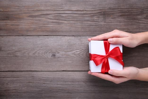 Mani femminili che tengono il contenitore di regalo sulla tavola di legno grigia