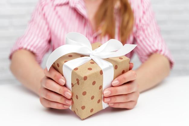 Mani femminili che tengono il contenitore di regalo