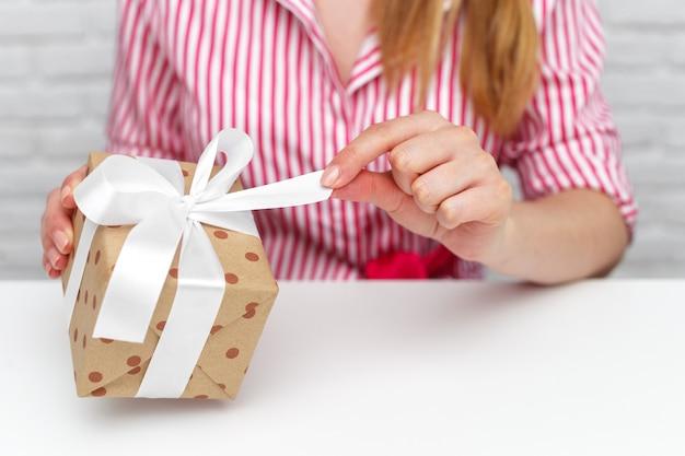 Mani femminili che tengono il contenitore di regalo.