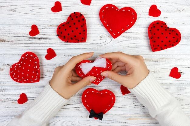 Mani femminili che tengono il cuore del giorno di biglietti di s. valentino sopra la tavola di legno.