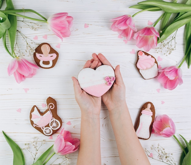 Mani femminili che tengono il cuore. una composizione per neonati su uno sfondo in legno.