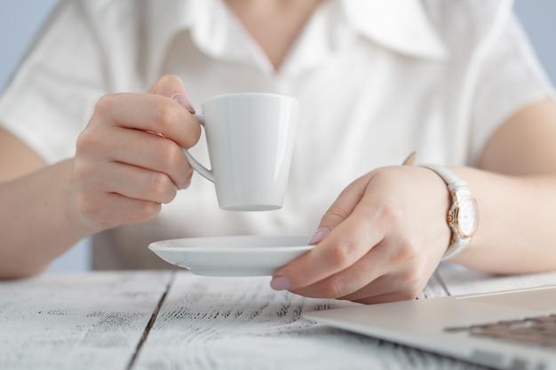 Mani femminili che tengono il primo piano della tazza di caffè. computer portatile gadget popolare, stile di vita moderno, vita aziendale, concetto di caffè del mattino