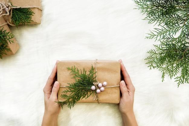 Mani femminili che tengono il regalo di natale