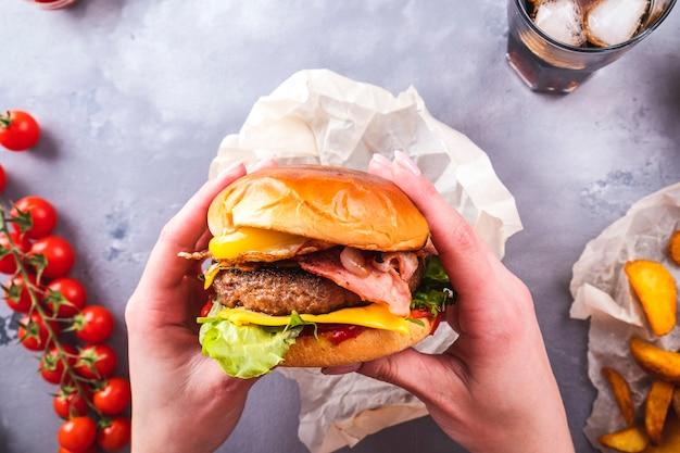 Mani femminili che tengono l'uovo fritto e il bacon succosi degli hamburger del manzo. vista dall'alto.