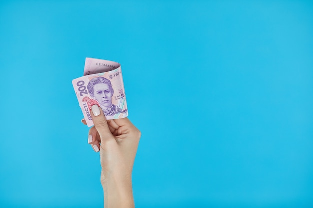 Mani femminili che tengono le banconote ucraine su fondo blu
