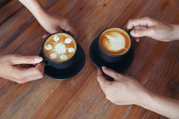 Mani femminili che tengono le tazze di caffè sul fondo di legno rustico della tavola