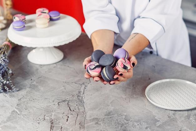 Mani femminili che tengono maccheroni francesi variopinti sopra una tavola di marmo.