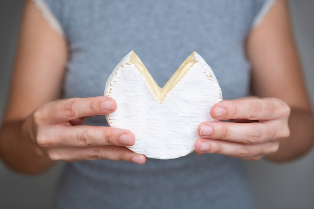 Mani femminili che tengono pezzo di formaggio a pasta molle