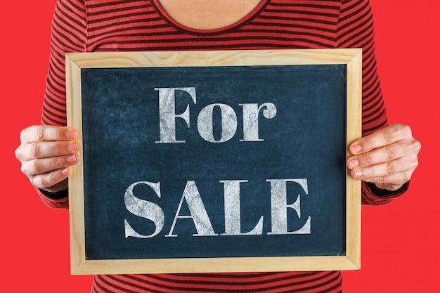 Mani femminili che tengono piccola lavagna nera davanti al corpo con le parole scritte che dicono per la vendita