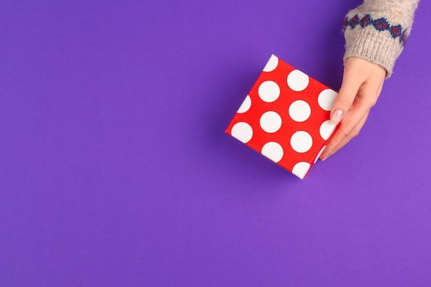 Mani femminili che tengono regalo avvolto su superficie viola
