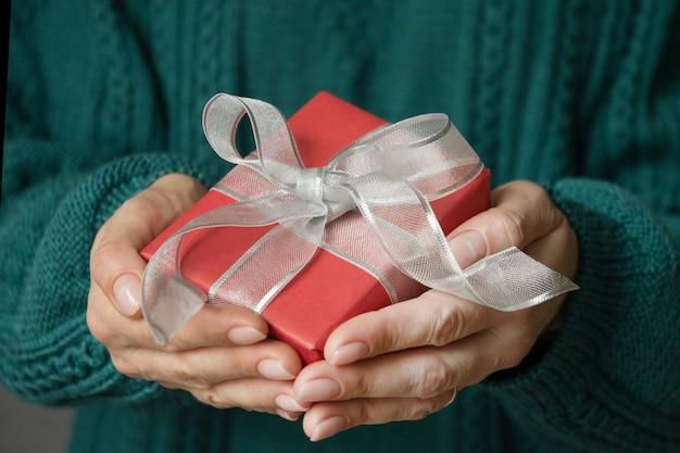 Mani femminili che tengono regalo rosso avvolto con nastro d'argento regalo di natale presente santo stefano