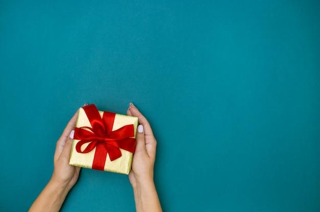 Mani femminili che tengono regalo su fondo blu