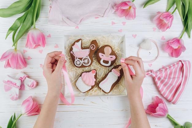 Mani femminili che tengono scatola con i biscotti. una composizione per i neonati