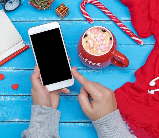 Mani femminili che tengono smart phone bianco con schermo nero vuoto