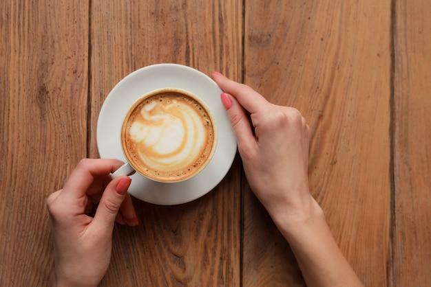 Mani femminili che tengono tazza con cappuccino di caffè con schiuma con motivo piacevole