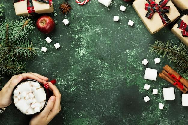 Mani femminili che tengono tazza con cioccolata calda e vari attributi della festa sulla vista grigia e superiore, spazio della copia