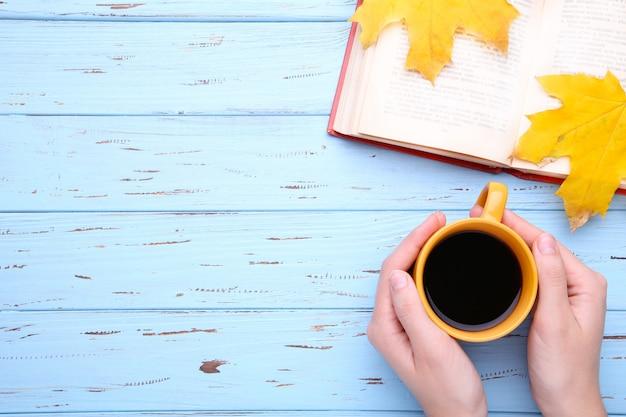 Mani femminili che tengono tazza di caffè nero con le foglie e il libro di autunno sulla tavola blu