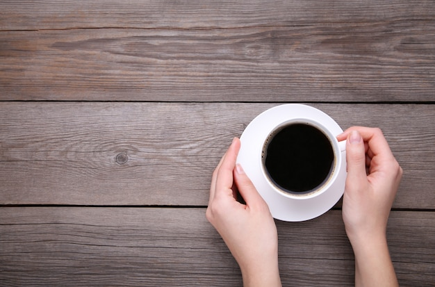 Mani femminili che tengono tazza di caffè su fondo di legno grigio.