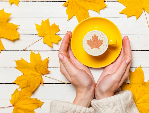 Mani femminili che tengono tazza di caffè sulla tavola di legno.