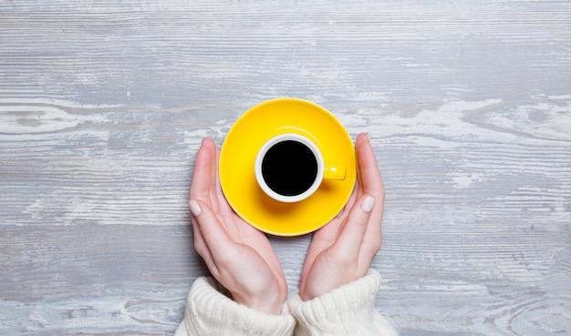 Mani femminili che tengono tazza di caffè.