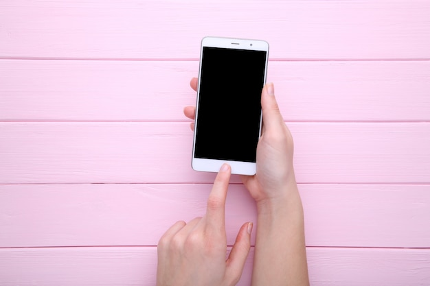 Mani femminili che tengono telefono cellulare con lo schermo in bianco su fondo di legno rosa. smartphone sul tavolo di legno.