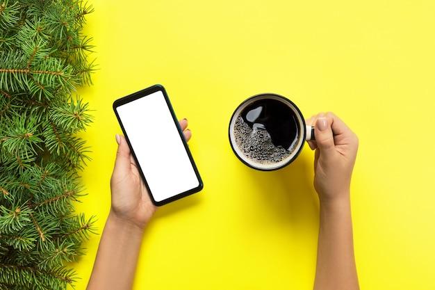 Mani femminili che tengono telefono cellulare nero con lo schermo e la tazza di caffè bianchi in bianco. immagine del modello con copyspace. vista dall'alto su sfondo giallo, piatto disteso