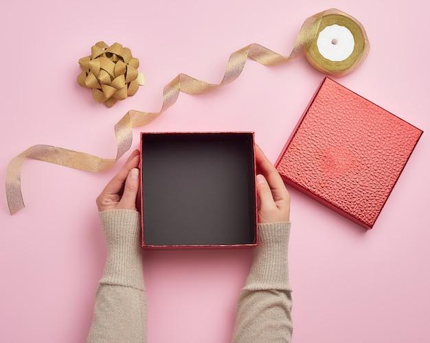 Mani femminili che tengono un contenitore di regalo vuoto quadrato