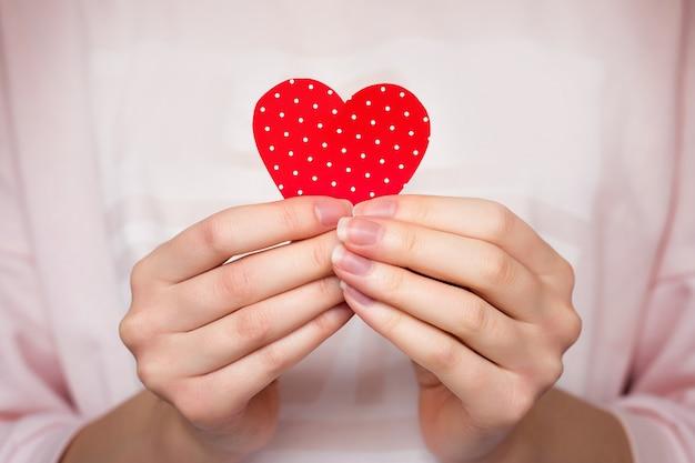 Mani femminili che tengono un cuore in sue mani