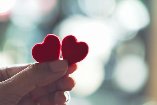Mani femminili che tengono un cuore rosso delle coppie, fuoco selettivo