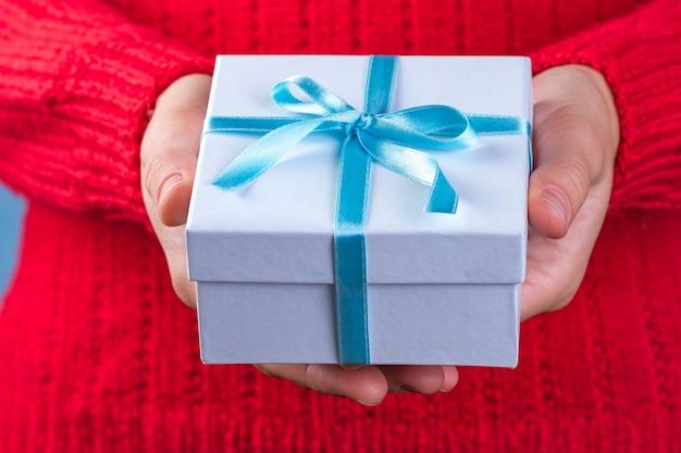 Mani femminili che tengono un piccolo contenitore di regalo bianco avvolto con il nastro blu. per dare e ricevere regali