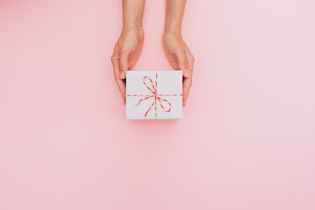 Mani femminili che tengono una confezione regalo bianca come regalo per natale, capodanno, festa della mamma o anniversario su uno sfondo di tavolo rosa, vista dall'alto