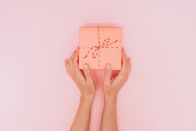 Mani femminili che tengono una grande confezione regalo come regalo per natale, capodanno, festa della mamma o anniversario su uno sfondo di tavolo rosa, vista dall'alto