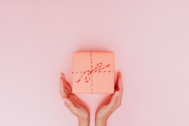 Mani femminili che tengono una grande confezione regalo come regalo per natale, capodanno, festa della mamma o anniversario su uno sfondo di tavolo rosa